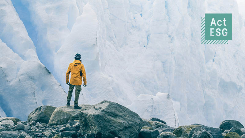 Climate change in sight: High-alpine shot of a person in outdoor clothing in front of a dramatic but still intact glacier scenery