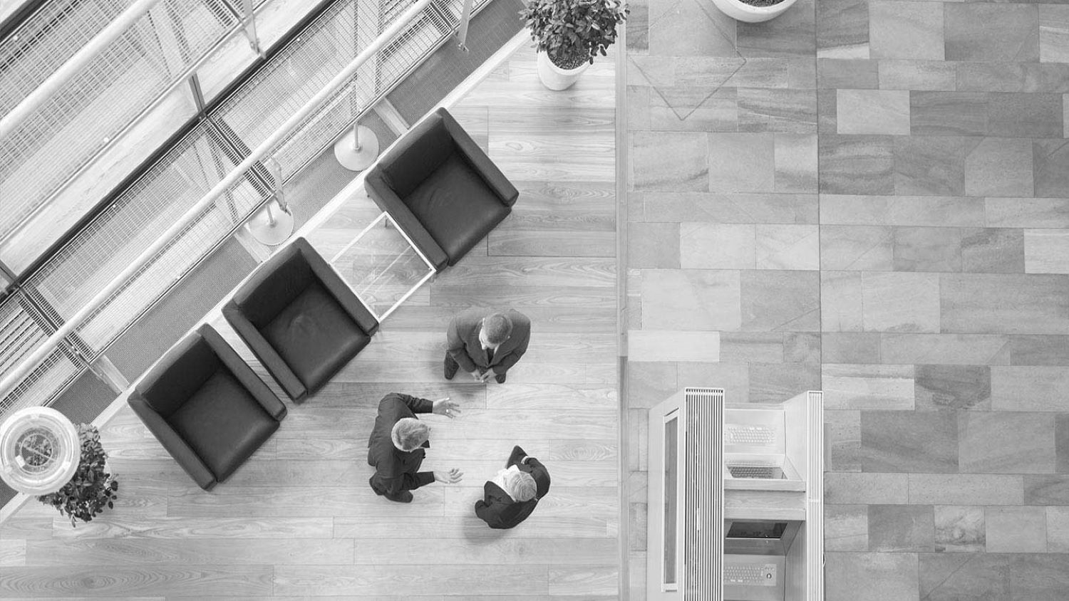 Picture from above. Three people greeting each other standing in a lobby.