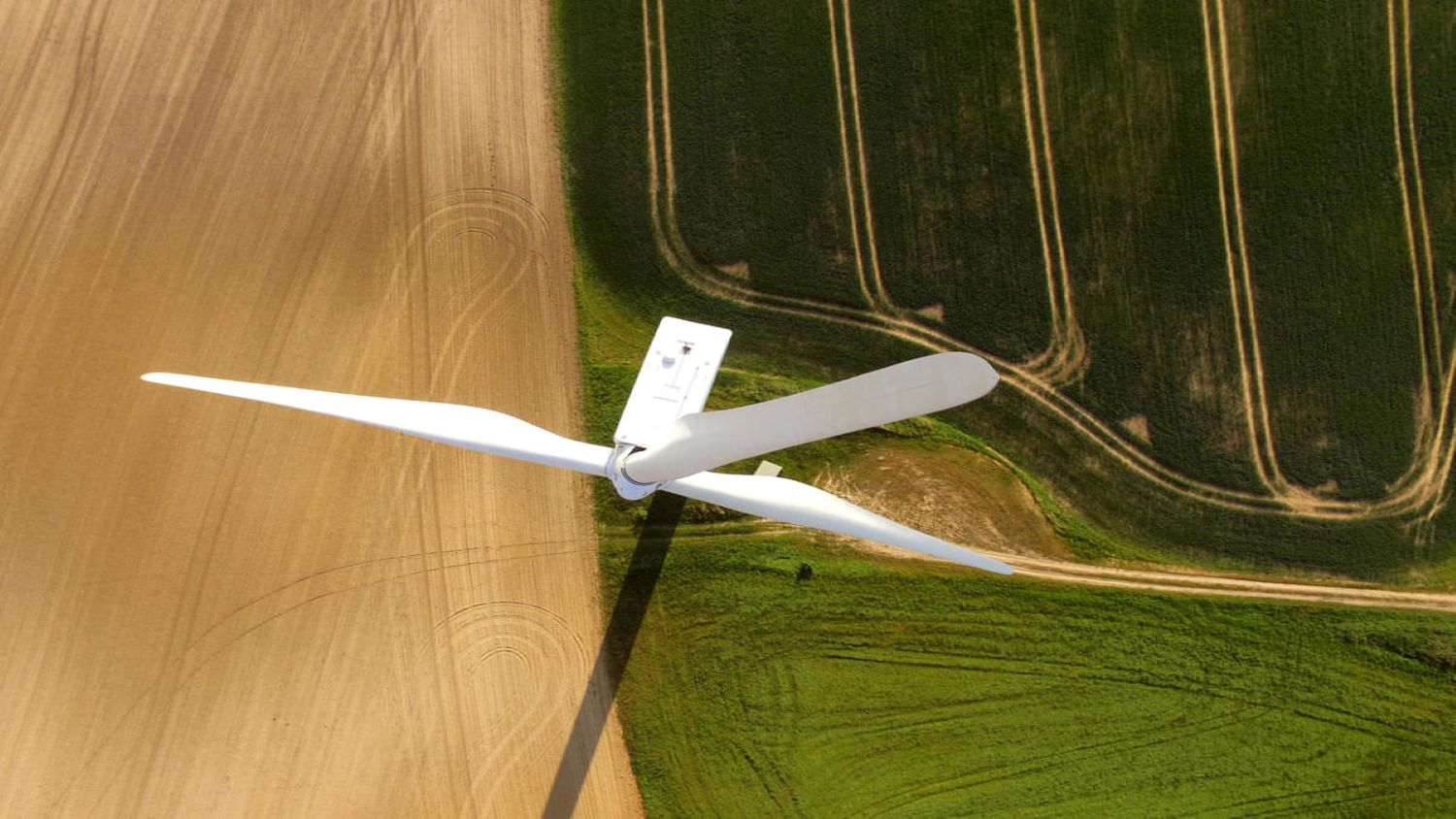 Close-up of the rotor blades of a wind turbine, photographed from above. Far down on the ground, one can see the traces that a tractor has left on an agricultural meadow.